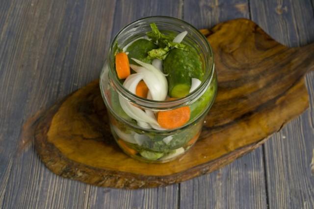 Укладываем в банку огурцы, чередуя морковью, луком и чесноком