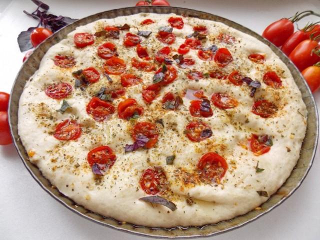 Распределяем по тесту помидоры и посыпаем специями и нарезанным базиликом