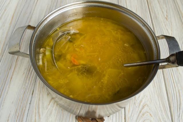 В кастрюлю с обжаренными овощами выливаем горячий бульон, кладём картофель и грибы, солим и готовим до готовности картофеля