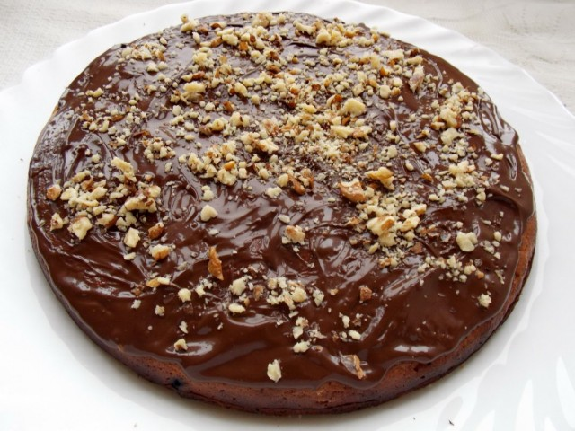Посыпаем шоколадную глазурь на кексе с вишней и черникой дроблёным орехом