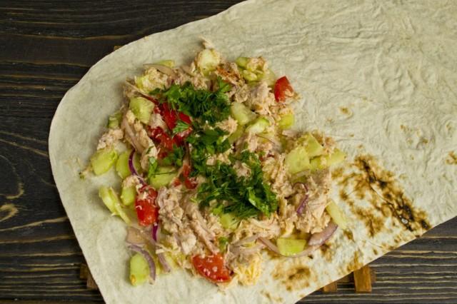 Выкладываем начинку из мяса и овощей на край лаваша и посыпаем рубленной зеленью