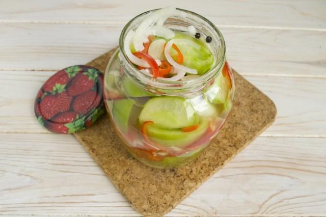 Перекладываем салат из зелёных помидоров с луком и перцем в стерилизованные банки и закручиваем