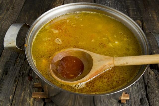 Выкладываем овощи в бульон, добавляем томатное пюре и готовим суп до полной готовности