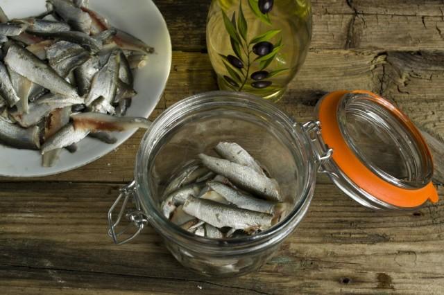 Выкладываем очищенную, солёную кильку в банку и заливаем растительным маслом