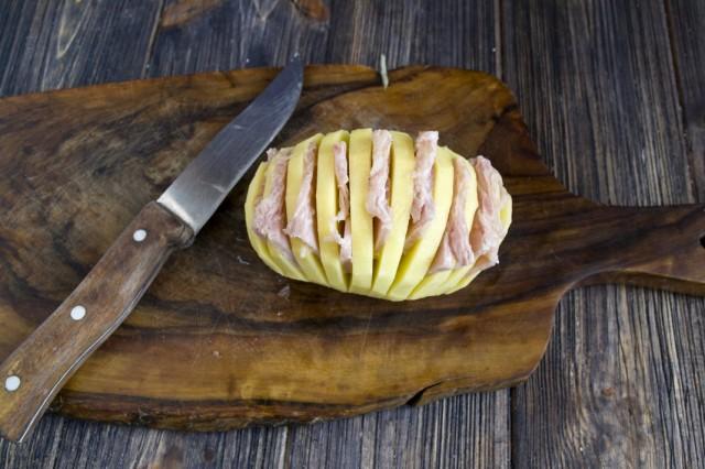 Нарезанную ветчину вставляем в надрезы на картофеле так, чтобы получилась гармошка