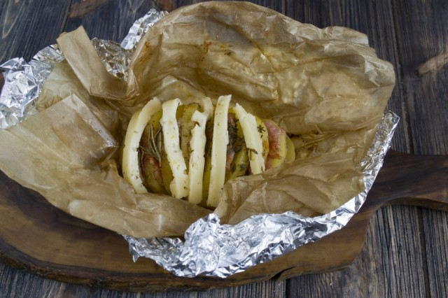 Нарезаем сыр, выкладываем его на почти готовый картофель и ставим обратно в духовку