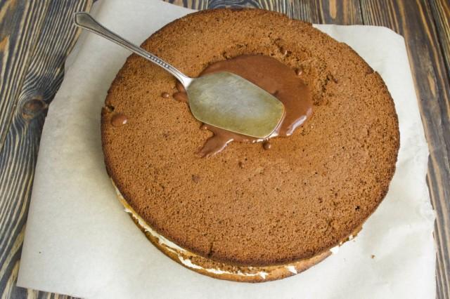 На верхний темный корж наносим глазурь и смазываем торт по бокам