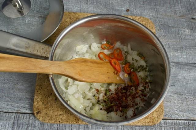 Добавляем в сотейник половинку нарезанного перца чили, паприку и молотый чёрный перец