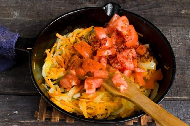 Добавляем нарезанные помидоры, сушеную паприку и перец чили. Тушим овощи 5-6 минут