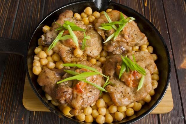 В сковороду перекладываем отваренный нут, сверху выкладываем тушёное мясо, поливаем соусом и ставим в духовку тушится на 5-8 минут при 230 градусах