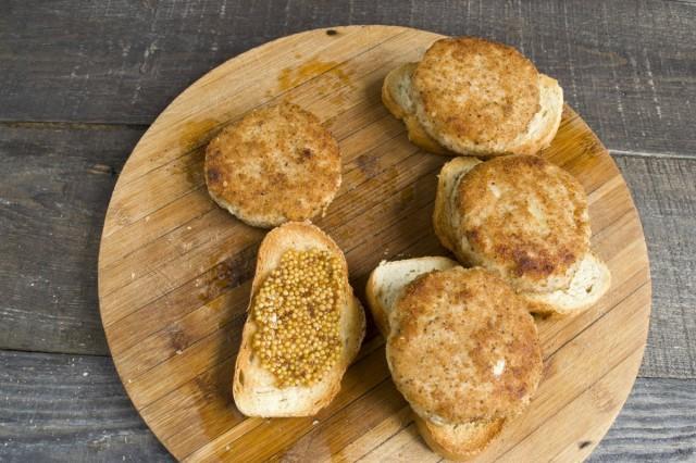 Намазываем на хлеб горчицу и кладём сверху котлету