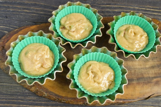 Перекладываем тесто для маффинов в смазанные маслом формочки для запекания