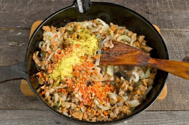 Обжариваем лук. Добавляем в сковороду грибы, сушеную морковь, кубик грибного бульона