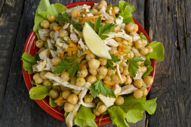 Выкладываем на листья салат с копченой курицей и нутом, поливаем свежевыжатым лимонным соком, перчим
