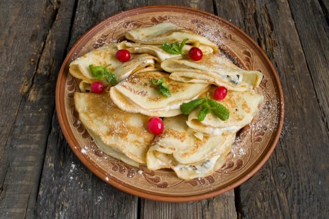 Посыпаем французские крепы с черносливом и творогом сахарной пудрой и украшаем мятой и ягодами