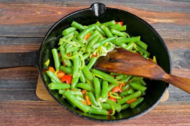 Насыпаем в сковородку зелёную стручковую фасоль и обжариваем овощи 10-12 минут