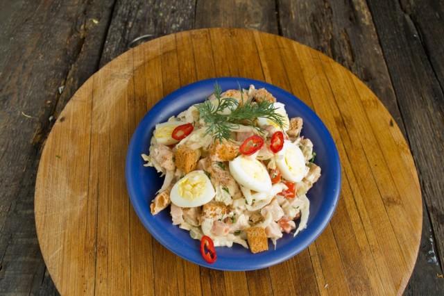 Накладываем салат с ветчиной в тарелку, нарезаем отваренные перепелиные яйца и подаём к столу