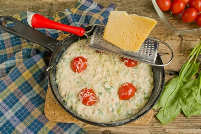Вдавливаем сверху помидоры черри и посыпаем сыром