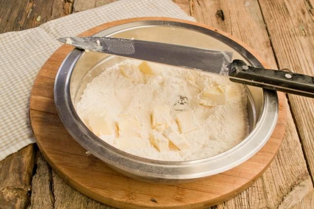 Добавляем нарезанное масло в миску с мукой