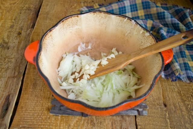 Лук и чеснок добавляем к растительному маслу в кастрюле
