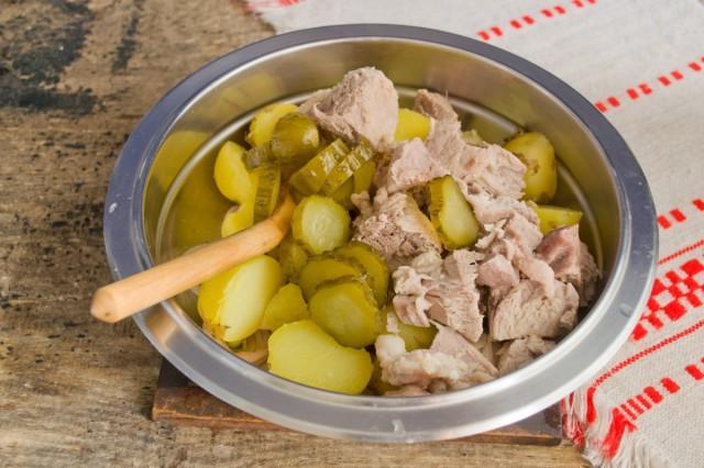 Добавляем в миску солёные огурцы и мясо