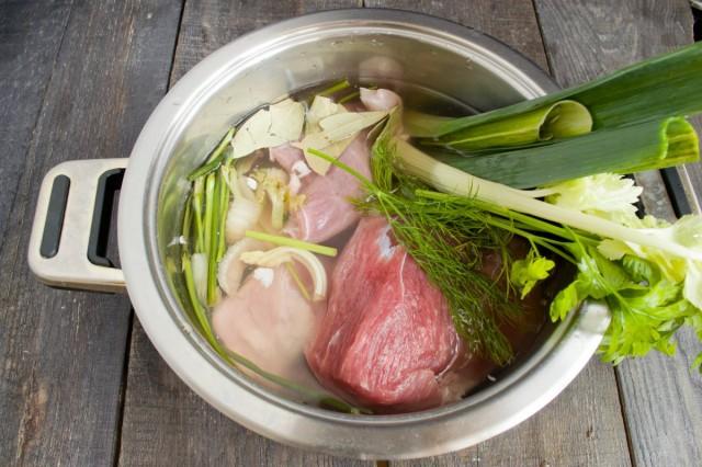 Кладем в кастрюлю свинину, зелень и соль
