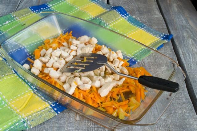 Обжариваем кусочки курицы, выкладываем на овощи в форме