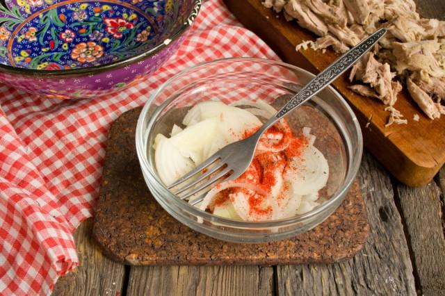 Сладкий салатный лук нарезаем, посыпаем солью и молотой паприкой