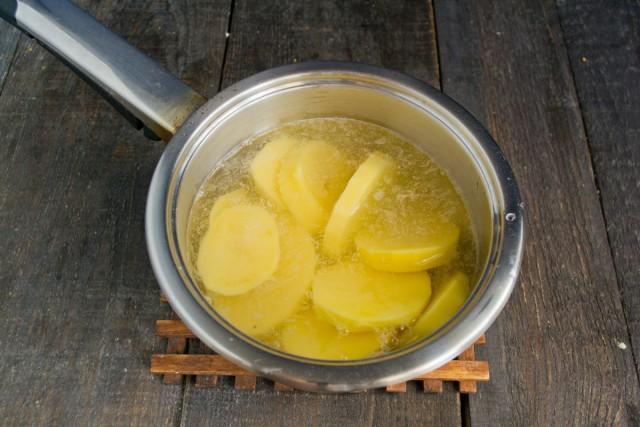 Бросаем картофель и чеснок в кипящую воду