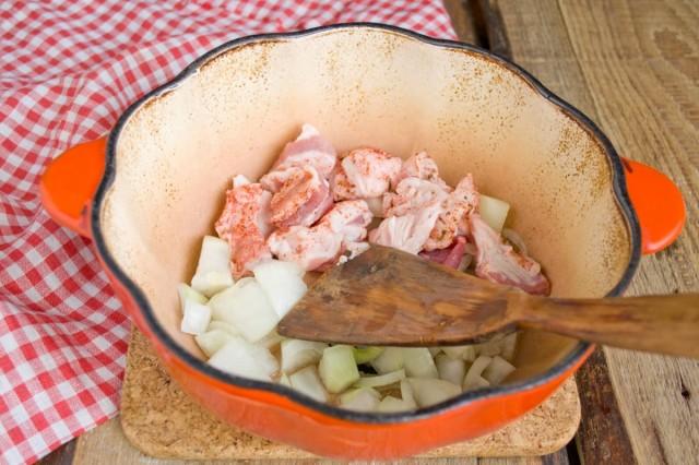 Бросаем в жаровню половину нарезанного лука, немного чеснока и часть свинины