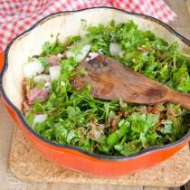 Выкладываем на свинину половину зелени, лук, оставшееся мясо и зелень, солим и перчим