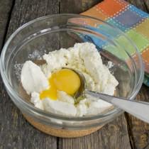Разбиваем в миску с творогом куриное яйцо