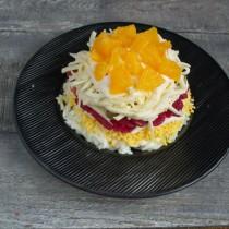 Нарезаем апельсин кубиками и выкладываем на сыр, смазанный майонезом