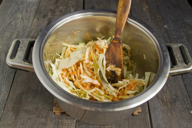 Добавляем шинкованную капусту, томатное пюре и 2-3 лавровых листочка