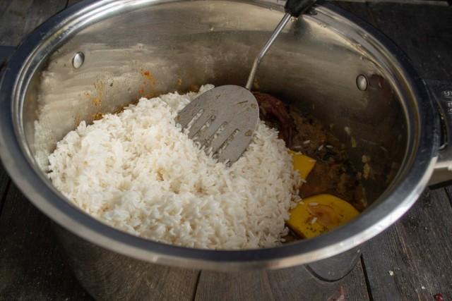 Добавляем рис, головку чеснока и горячую воду
