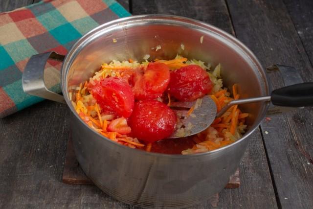 Добавляем консервированные томаты и сливочное масло. Доводим до кипения, убавляем огонь и готовим 10 минут