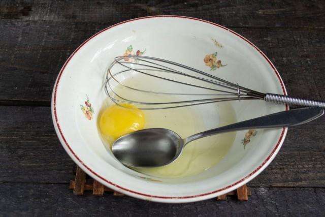 Наливаем в миску оливковое масло, солим и разбиваем куриное яйцо