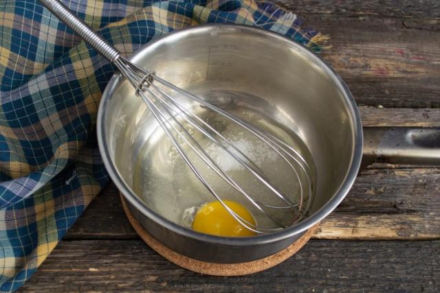 Разбиваем в сотейник свежее яйцо, насыпаем сахарный песок