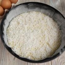 Смазываем форму маслом, присыпаем мукой, выкладываем тесто и посыпаем кокосовой стружкой