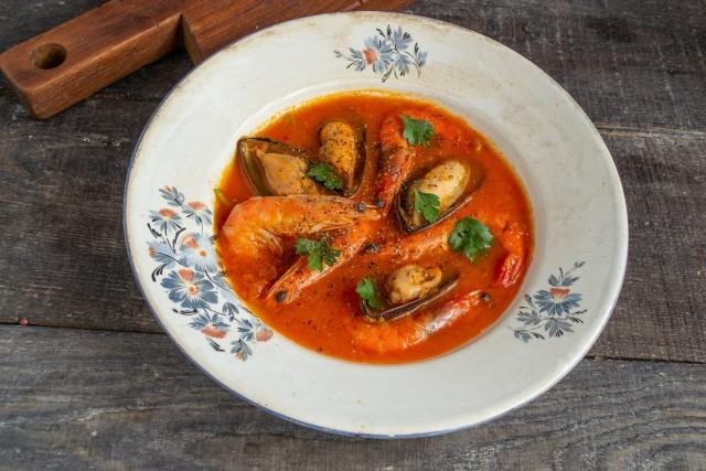 Выкладываем морепродукты в тарелки, наливаем суп, перчим и украшаем зеленью. Готово!
