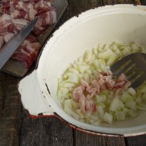 Срезаем немного жира и режем мелкими кубиками. Обжариваем лук и вытапливаем сало