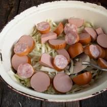 Кладём порезанную копченую колбасу и свиные сардельки на капусту