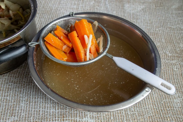 Достаём говядину из кастрюли и процеживаем бульон, оставляем морковь