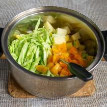 Кладём в кастрюлю нарезанные овощи: молодую капусту, картофель и болгарский перец