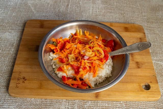 Смешиваем варёный рис с овощами, посыпаем молотым перцем, солим по вкусу и тщательно перемешиваем