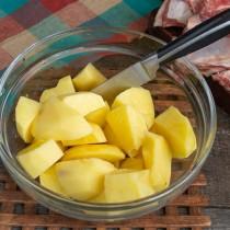 Нарезаем крупно картофель и заливаем холодной водой