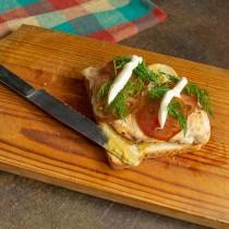 Кладём на филе помидор и укроп. Выдавливаем тонкие полоски майонеза