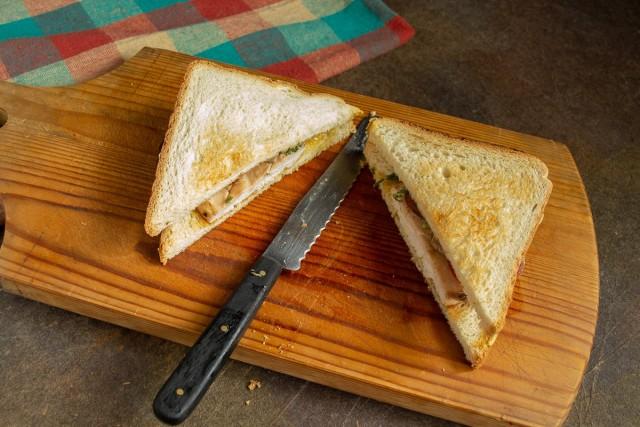 Кладём второй ломтик хлеба и разрезаем по диагонали. Вкусный сэндвич с курицей и помидором готов!
