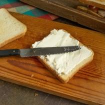 Для сэндвича с огурцом на два подрумяненных тоста намазываем творожный сливочный сыр