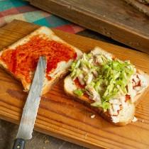 На ломтик хлеба кладём нарезанное мясо, затем щедрую щепоть капусты